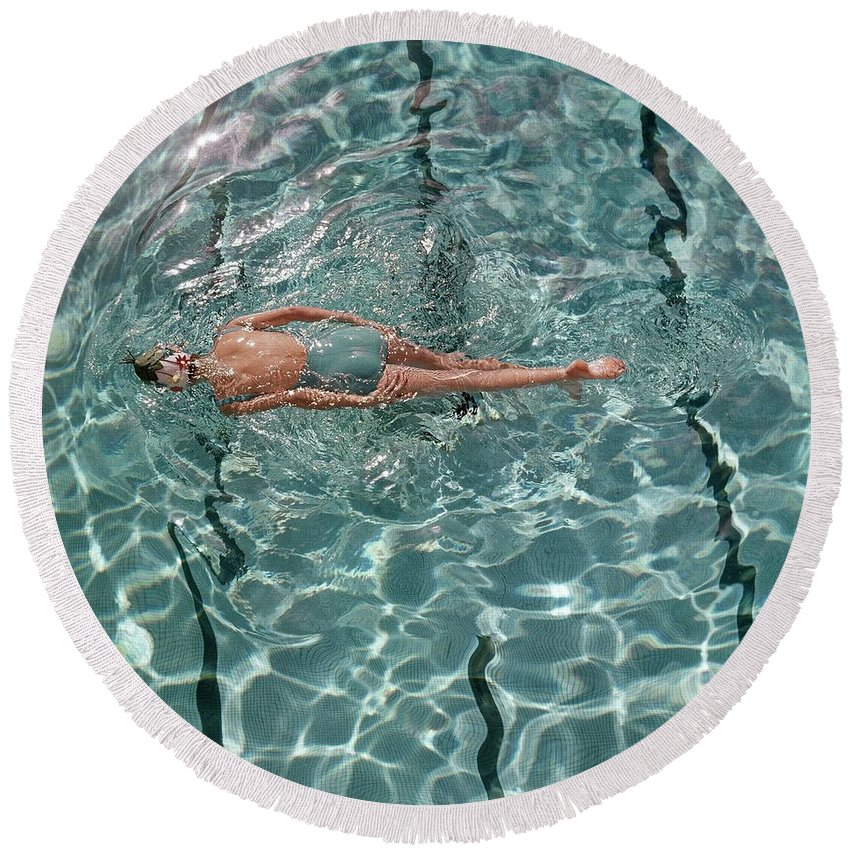 Water Round Beach Towel featuring the photograph A Woman Swimming In A Pool by Fred Lyon