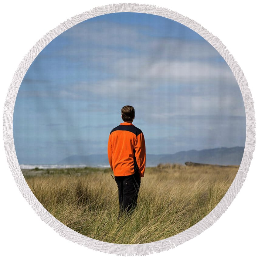 Alone Round Beach Towel featuring the photograph A Young Man Stands In A Field by Michael Hanson