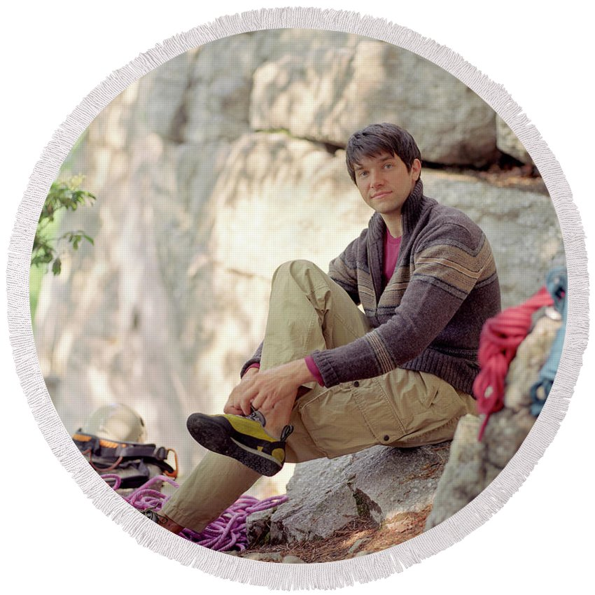 25-30 Years Round Beach Towel featuring the photograph A Young Rock Climber Puts On A Climbing by Matthew Wakem