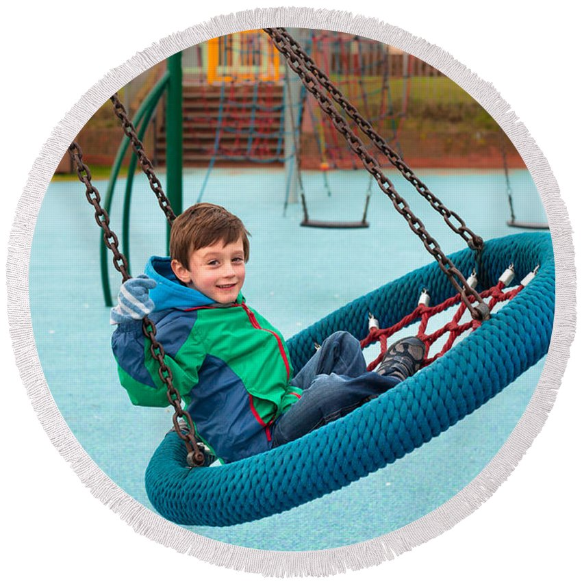 Action Round Beach Towel featuring the photograph Boy On Swing by Tom Gowanlock