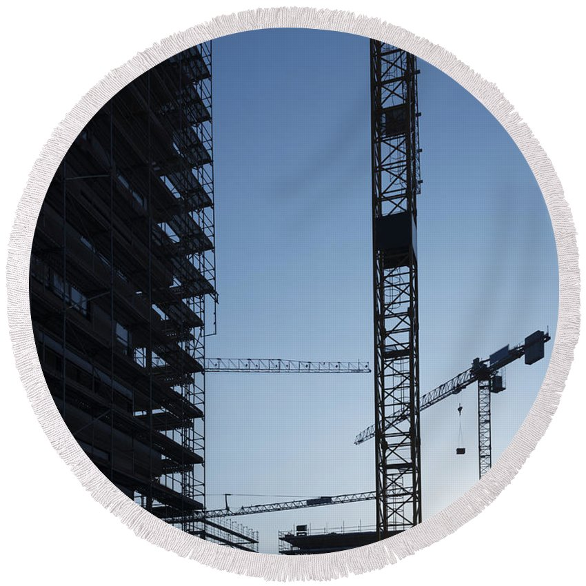 Construction Crane Round Beach Towel featuring the photograph Construction Cranes In Backlit by Mats Silvan