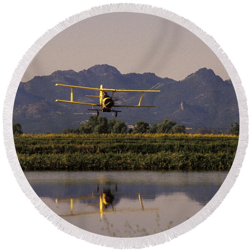 Agriculture Round Beach Towel featuring the photograph Crop Duster Applying Seed To Rice Field by Ron Sanford