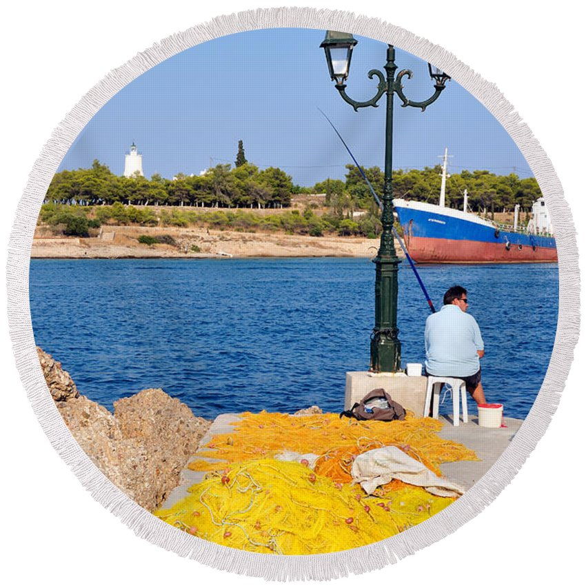 Spetses; Old; Harbor; Port; Man; Adult; Fish; Fishing; Nets; Yellow; Ship; Vessel; Greece; Greek; Hellas; Argosaronic; Saronic; Gulf; Town; City; Chora; Islands; Sea; Island; Holidays; Vacation; Travel; Trip; Voyage; Journey; Tourism; Touristic; Summer; Pole; Post; Light Round Beach Towel featuring the photograph Fishing In Spetses Town by George Atsametakis