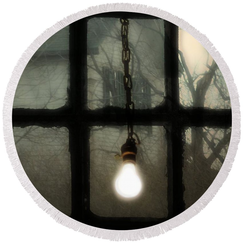 Old Light Bulb Round Beach Towel featuring the photograph Lit Light Bulb Shines In Old Window by Gothicrow Images