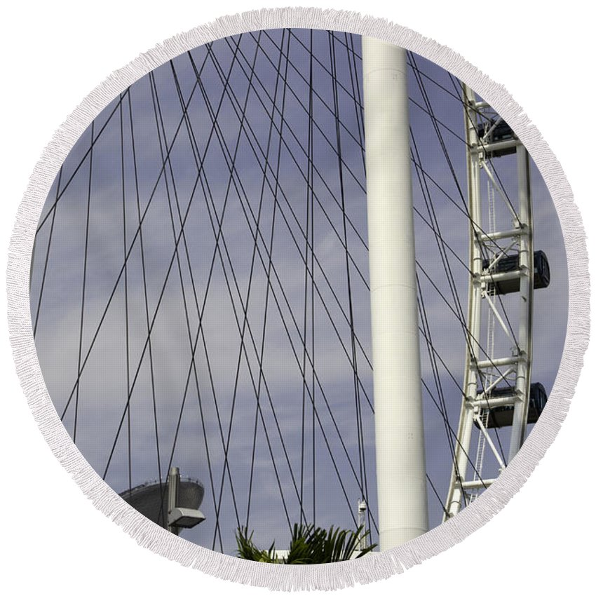 Action Round Beach Towel featuring the photograph The Top Section Of The Marina Bay Sands As Seen Through The Spokes Of The Singapore Flyer by Ashish Agarwal