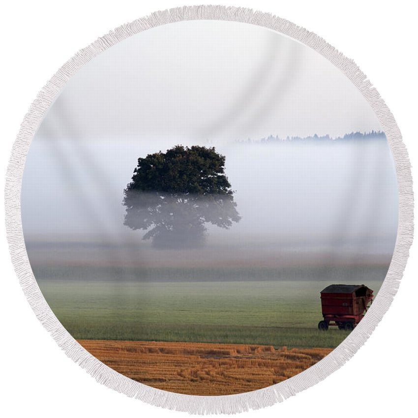 Agriculture Round Beach Towel featuring the photograph Tractor In Field Low Fog With Tree And Harvester by Jim Corwin