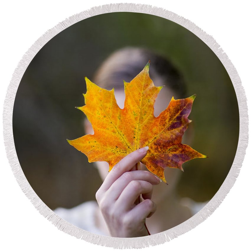 Autumn Round Beach Towel featuring the photograph Woman Holding An Autumnal Leaf by Lee Avison