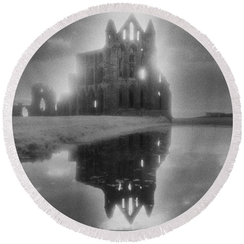 Eerie; Atmospheric; Spooky; Haunted; Haunting; Dramatic; Striking; Misty; Hazy; Lake; Reflection; English; Architecture; Exterior; Ruin; Ruins Round Beach Towel featuring the photograph Whitby Abbey by Simon Marsden