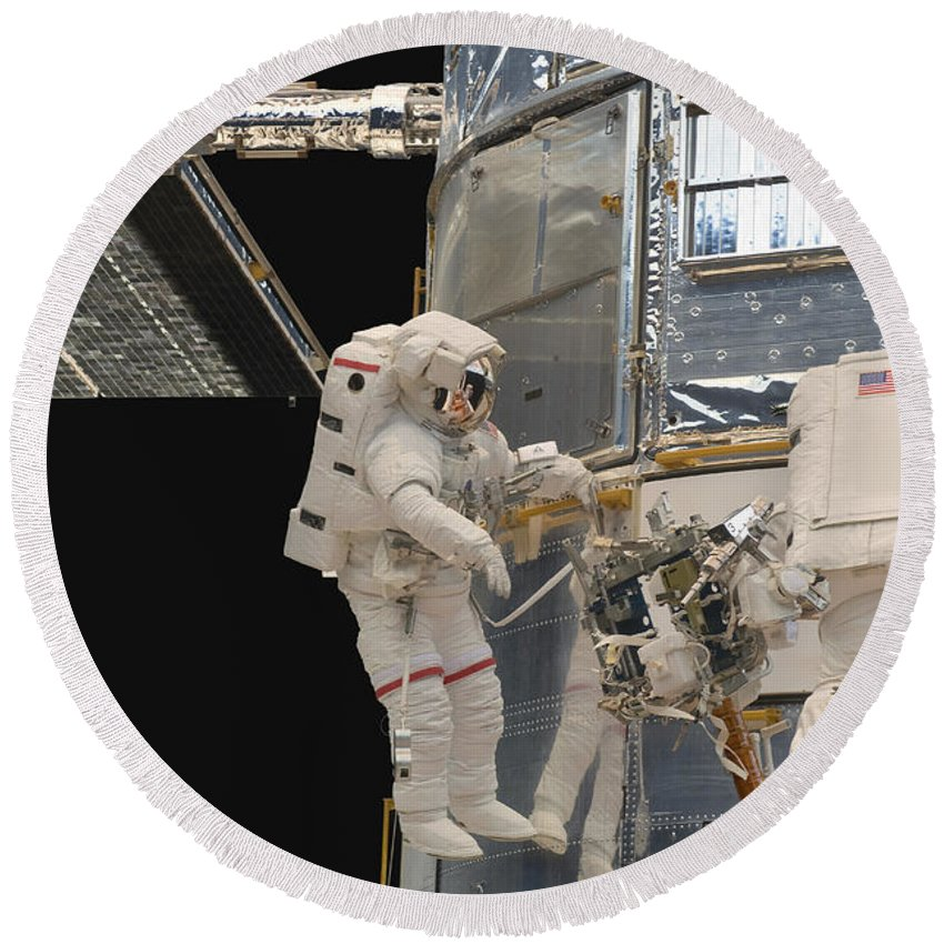 Sts-125 Round Beach Towel featuring the photograph Astronauts Working On The Hubble Space by Stocktrek Images