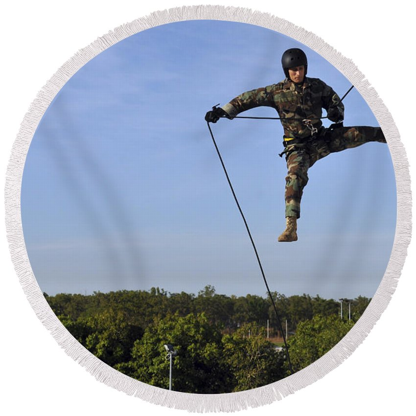 Rappelling Round Beach Towel featuring the photograph Soldier Rappels Off A Tower While by Stocktrek Images