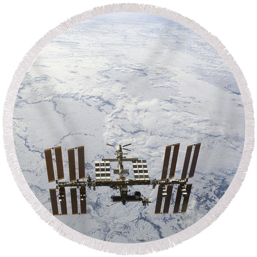 View From Space Round Beach Towel featuring the photograph The International Space Station by Stocktrek Images