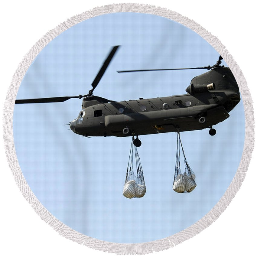 National Guard Round Beach Towel featuring the photograph A Ch-47 Chinook Carrying Sandbags by Stocktrek Images