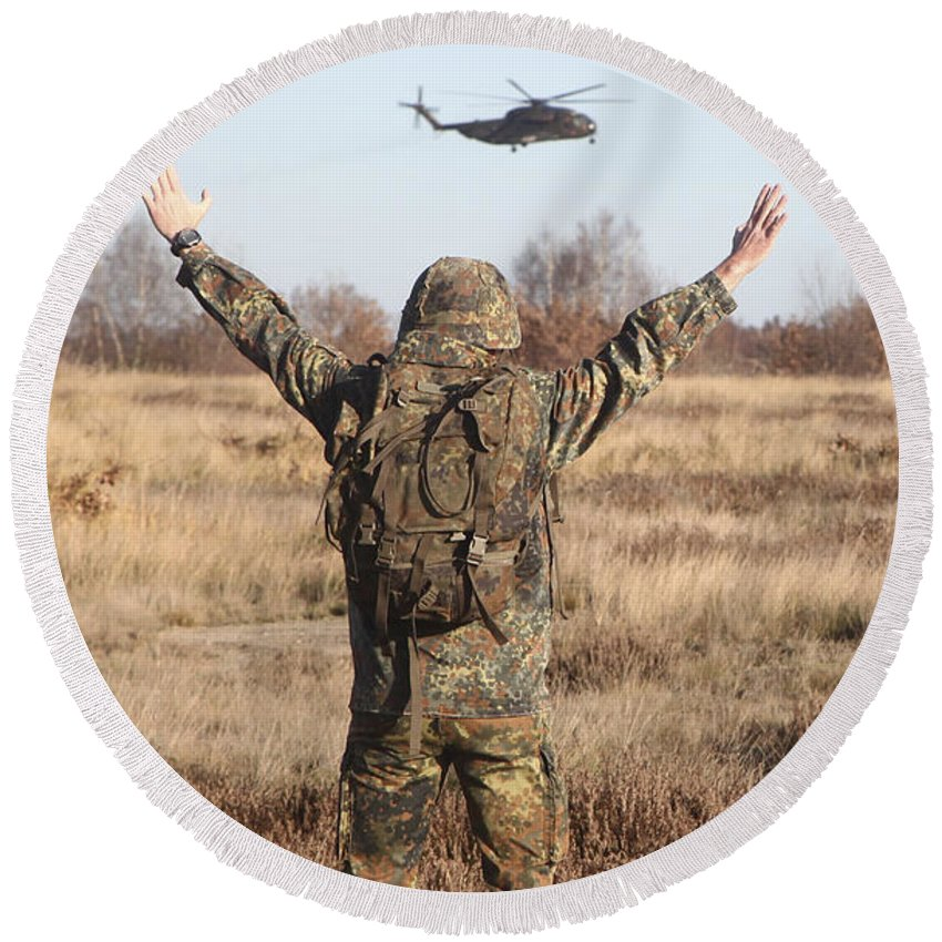 Germany Round Beach Towel featuring the photograph A German Army Soldier Guides A Ch-53gs by Timm Ziegenthaler