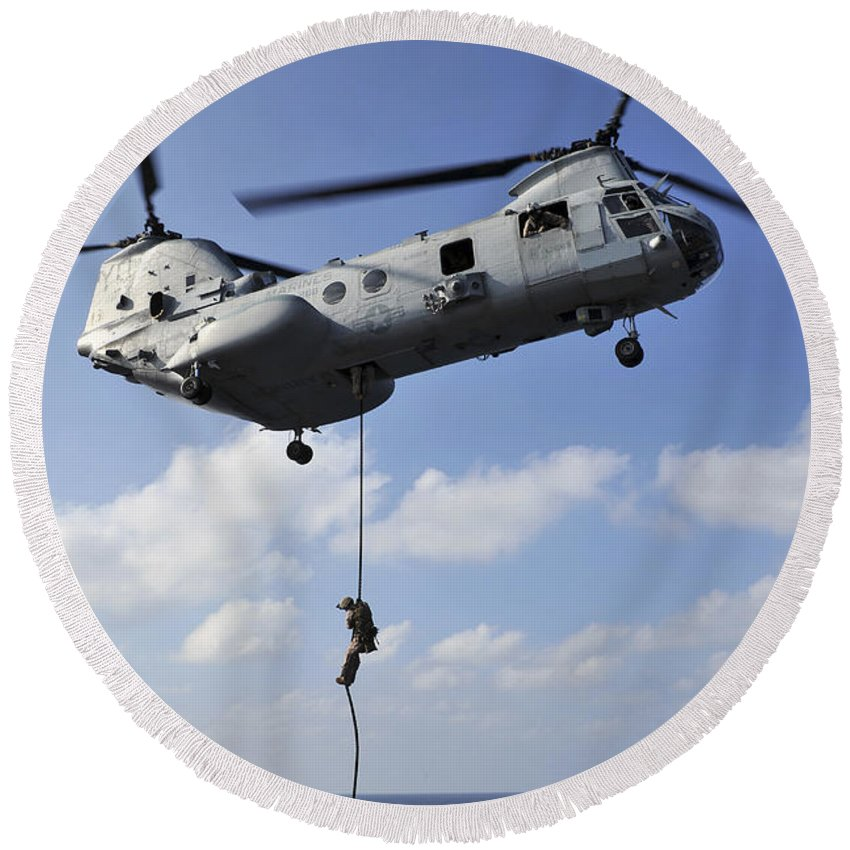 Military Round Beach Towel featuring the photograph A Marine Fast Ropes From A Ch-46e Sea by Stocktrek Images