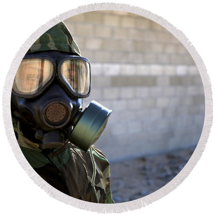 Protective Clothing Round Beach Towel featuring the photograph A Marine Wearing A Gas Mask by Stocktrek Images