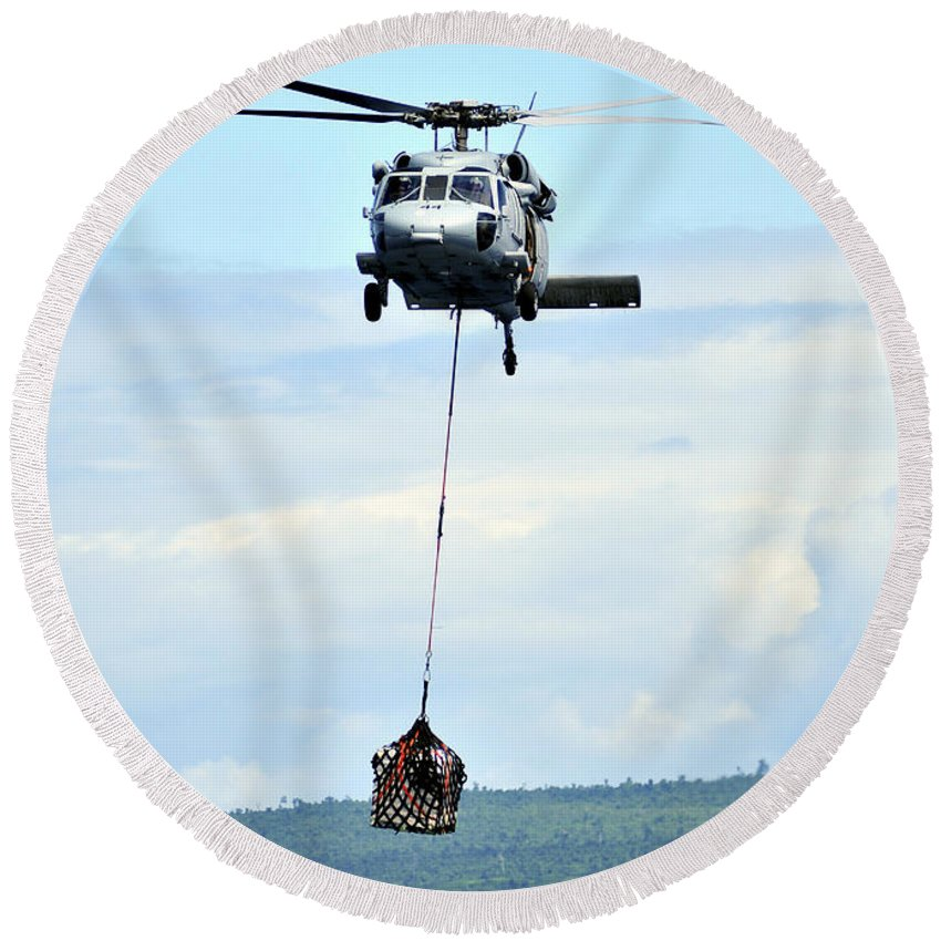 Mh-60 Round Beach Towel featuring the photograph A Mh-60 Knighthawk Carries Supplies by Stocktrek Images