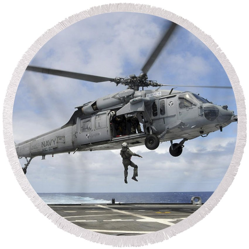 Rimpac Round Beach Towel featuring the photograph A Naval Aircrewman Is Hoisted Into An by Stocktrek Images