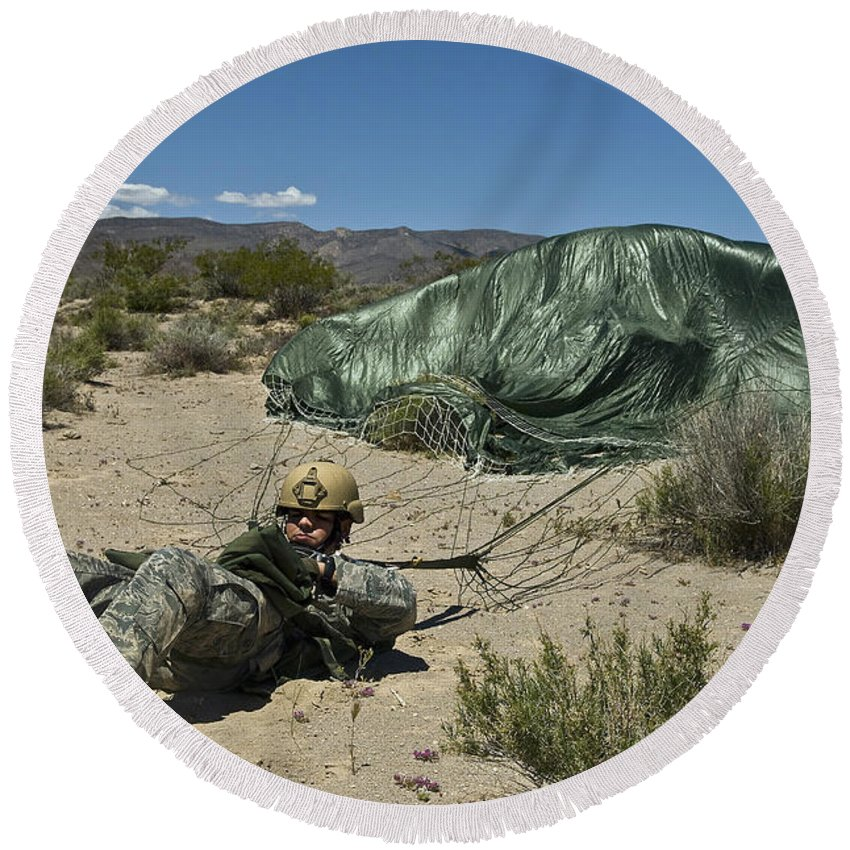 Parachuting Round Beach Towel featuring the photograph A Paratrooper Recovers After Landing by Stocktrek Images