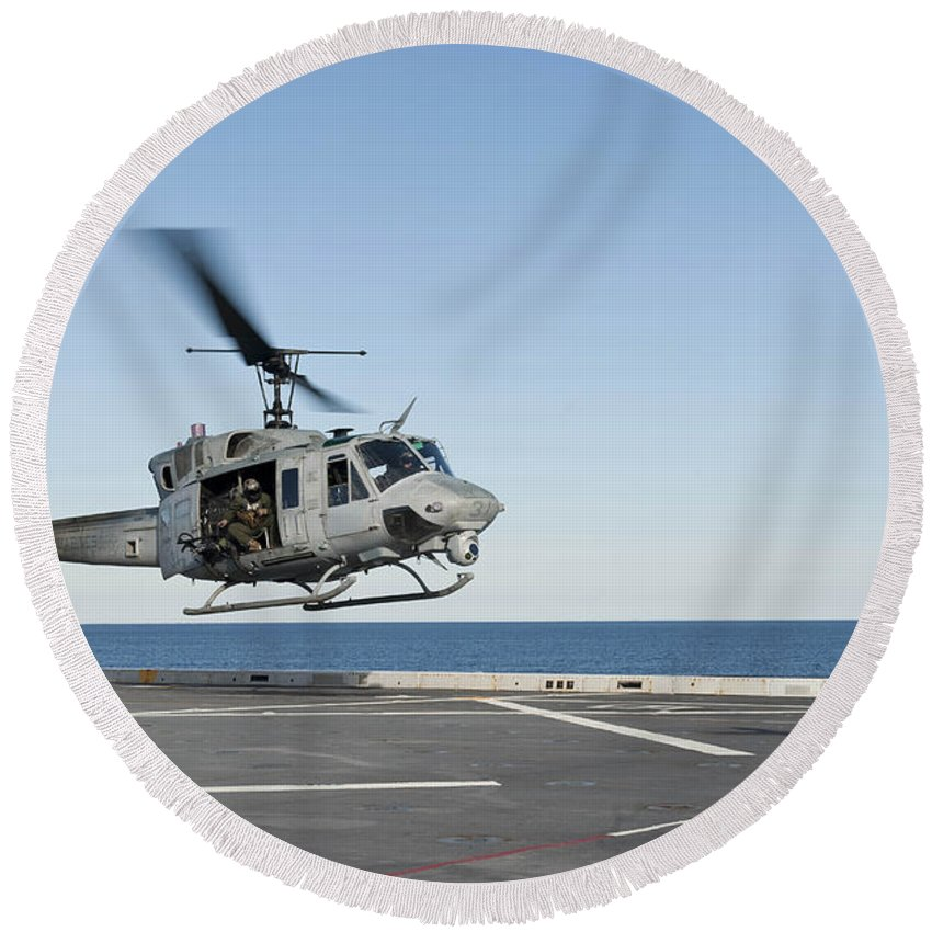 Military Round Beach Towel featuring the photograph A Sailor Directs A Uh-1n Huey by Stocktrek Images