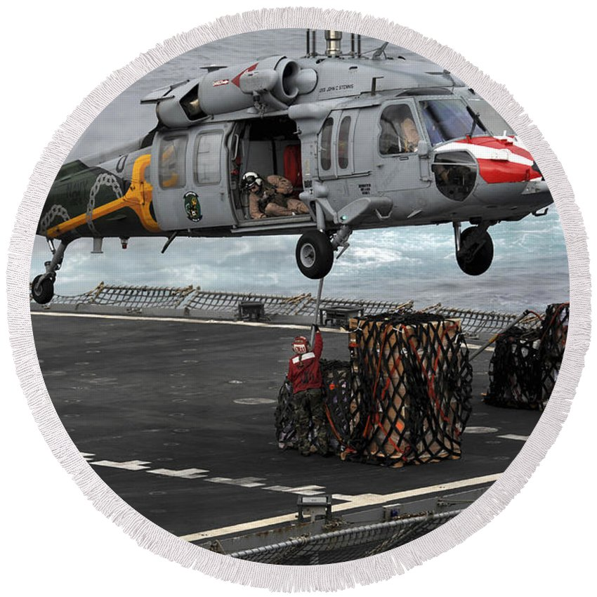 Operation New Dawn Round Beach Towel featuring the photograph A Sailor Hooks Cargo To An Mh-60s Sea by Stocktrek Images