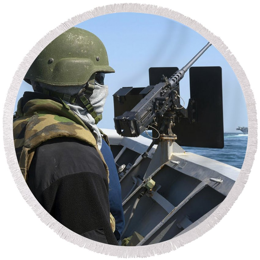 Military Round Beach Towel featuring the photograph A Sailor Manning A .50-caliber Machine by Stocktrek Images