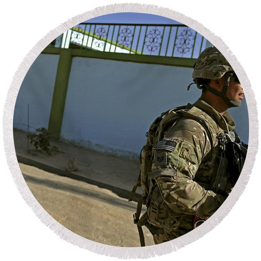 Provincial Reconstruction Team Round Beach Towel featuring the photograph A Soldier Patrols The Streets Of Qalat by Stocktrek Images