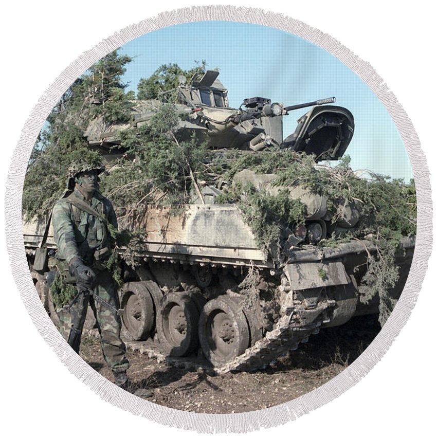 Battletank Round Beach Towel featuring the photograph A Soldier Stands Beside A Camouflaged by Stocktrek Images