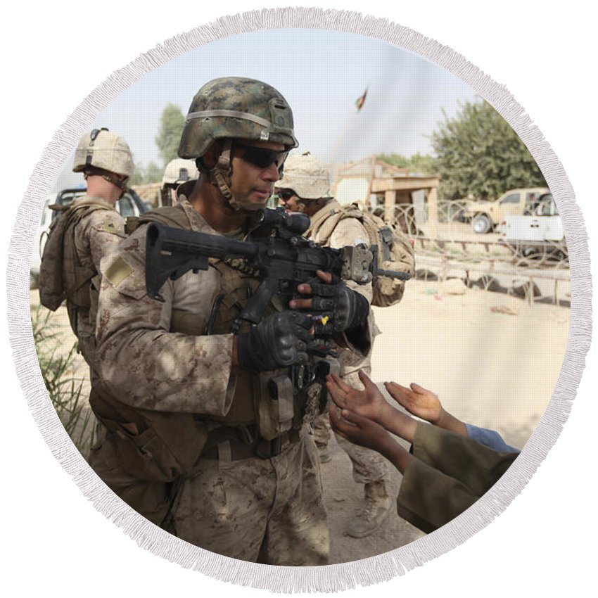 Operation Enduring Freedom Round Beach Towel featuring the photograph A U.s. Marine Gives A Piece Of Candy by Stocktrek Images