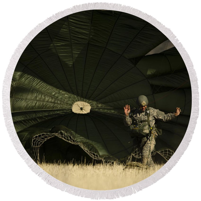 Military Round Beach Towel featuring the photograph A U.s. Soldier Collapses His Parachute by Stocktrek Images