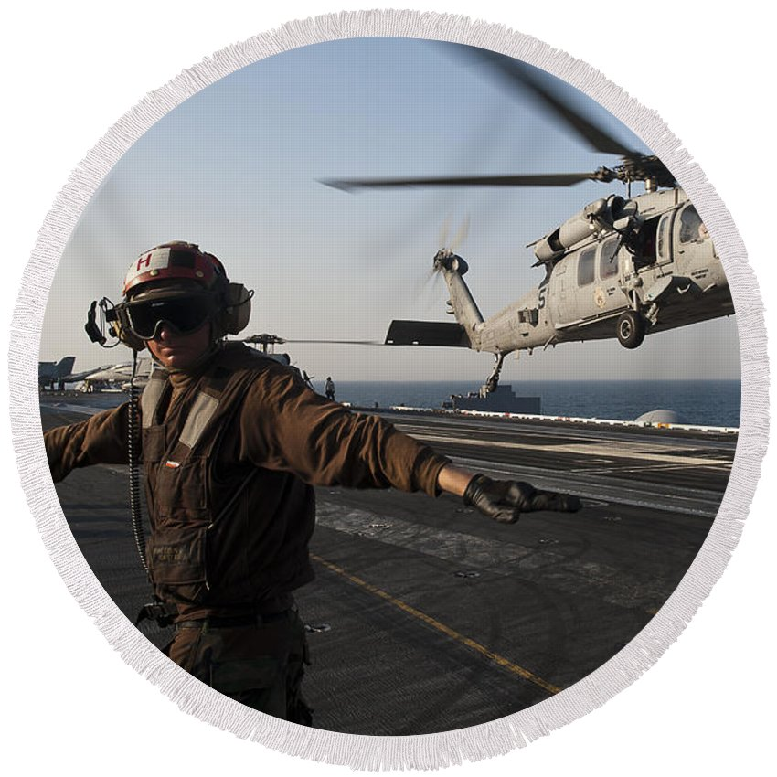 Operation New Dawn Round Beach Towel featuring the photograph Airman Checks For A Clear Deck As An by Stocktrek Images