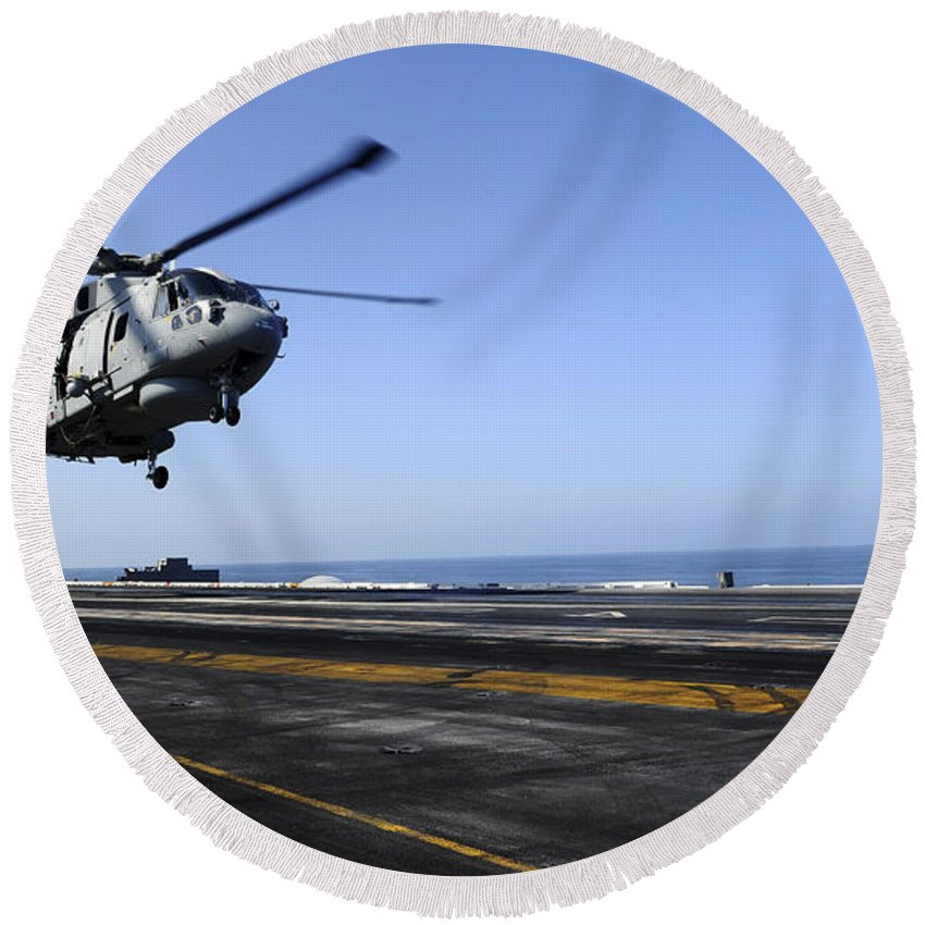 Uss John C Stennis Round Beach Towel featuring the photograph Airman Directs An Eh-101 Merlin by Stocktrek Images