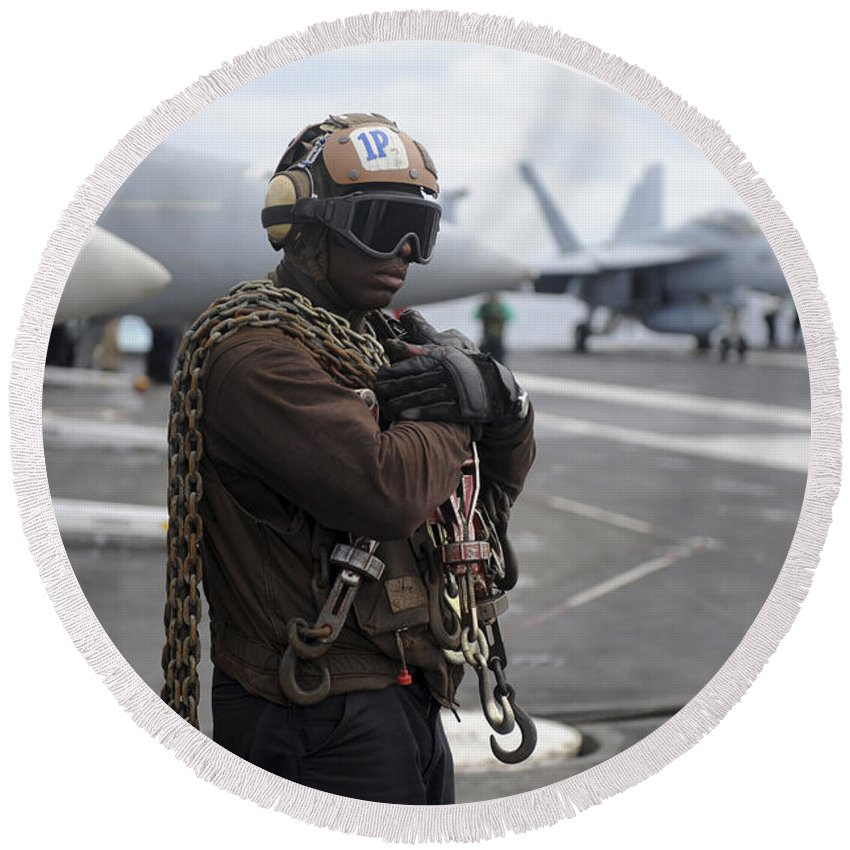 Flight Operations Round Beach Towel featuring the photograph Airman Stands By With Tie-down Chains by Stocktrek Images