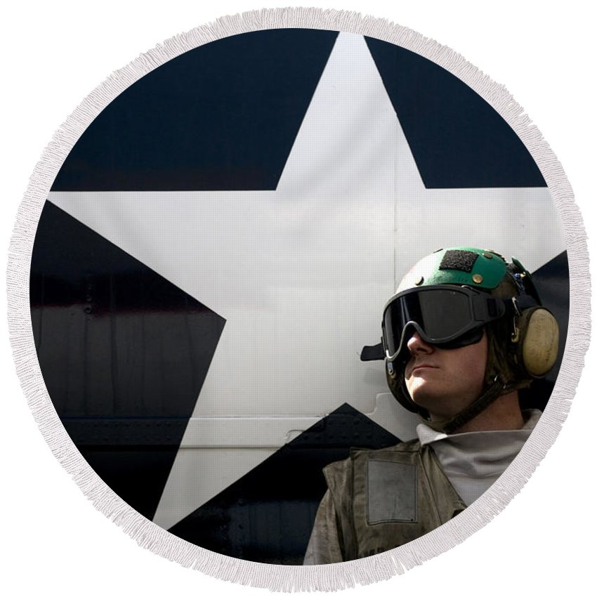 Uss Carl Vinson Round Beach Towel featuring the photograph An Airman Stands In Front Of A C-2a by Stocktrek Images