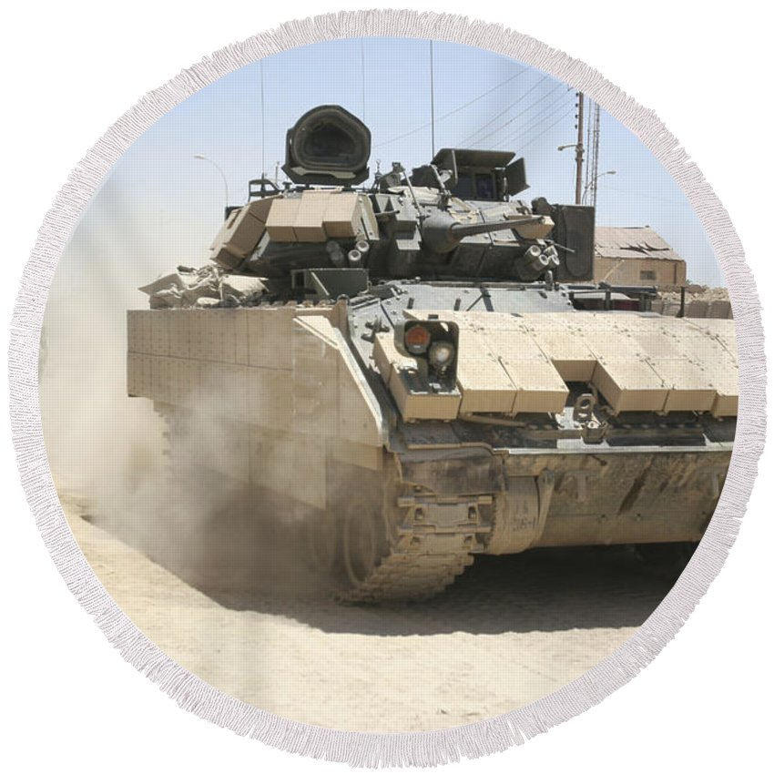Army Round Beach Towel featuring the photograph An M2 Bradley Fighting Vehicle Patrols by Stocktrek Images