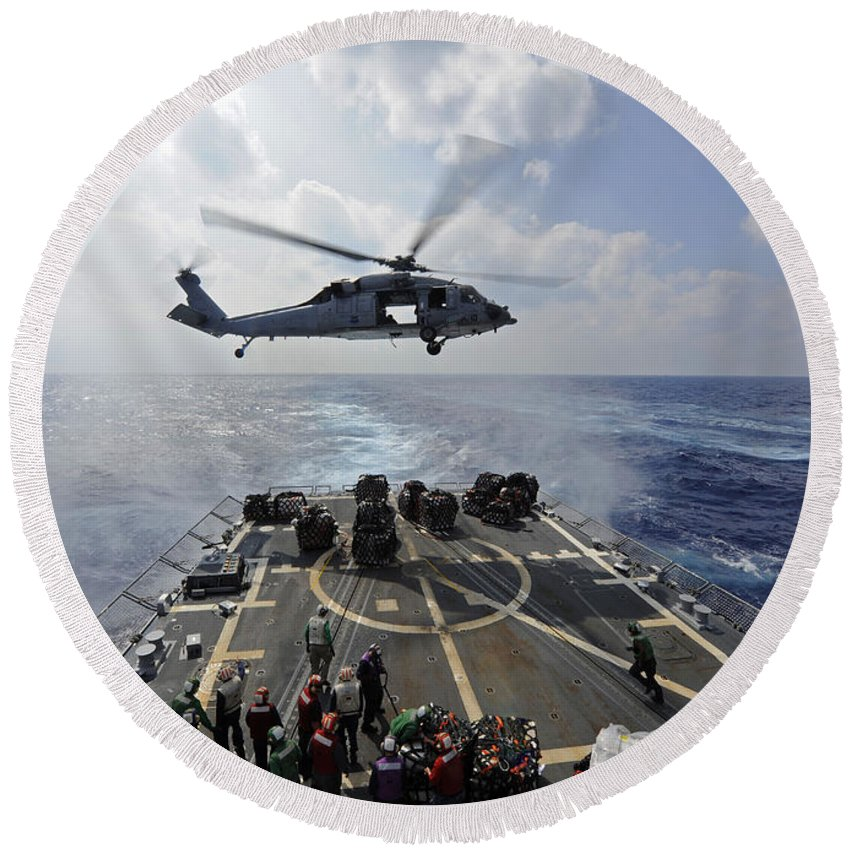 Dry Cargo Ships Round Beach Towel featuring the photograph An Mh-60r Sea Hawk Transfers Supplies by Stocktrek Images