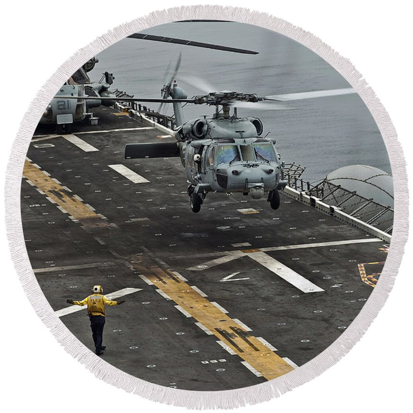Pacific Ocean Round Beach Towel featuring the photograph An Mh-60s Sea Hawk Lands Aboard by Stocktrek Images