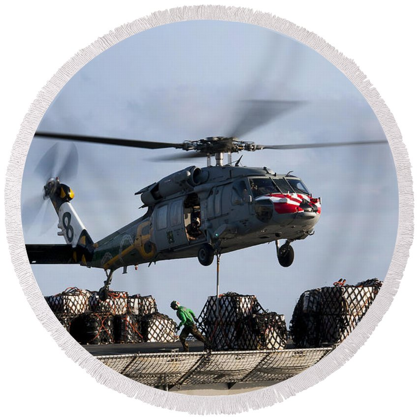 Operation New Dawn Round Beach Towel featuring the photograph An Mh-60s Sea Hawk Lifts Cargo by Stocktrek Images