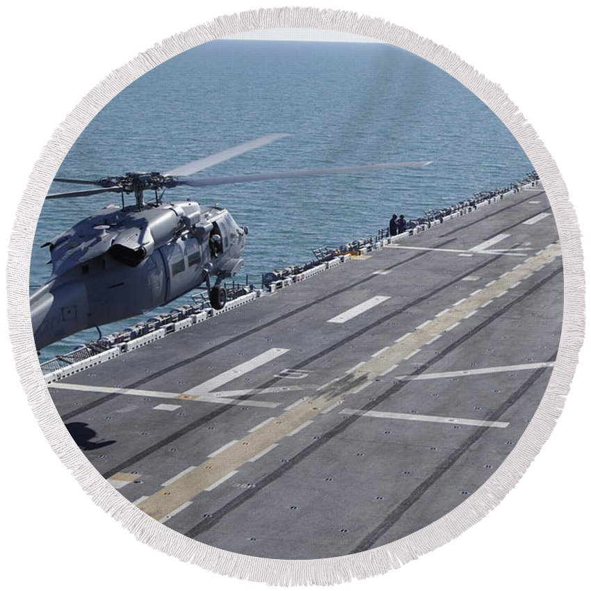 Uss Kearsarge Round Beach Towel featuring the photograph An Sh-60 Sea Hawk Helicopter Lands by Stocktrek Images