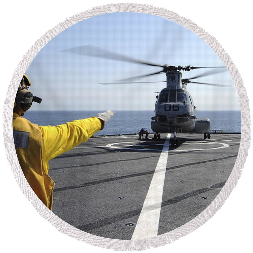 Guidance Round Beach Towel featuring the photograph Boatswain's Mate Directs A Ch-46 Sea by Stocktrek Images