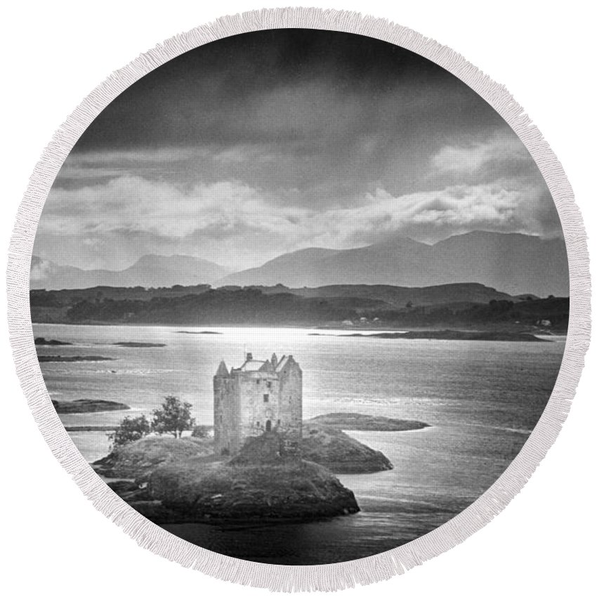 Medieval; Scottish; Landscape; Lake; Ominous; Foreboding; Brooding; Stormy Weather; Clouds; Dark; Mountains; Mountainous; Island; Exterior; Architecture; Gothic; Striking; Dramatic; Eerie; Mysterious; Mystery; Haunting; Haunted; Sinister; Spooky; Ghostly; Ethereal Round Beach Towel featuring the photograph Castle Stalker by Simon Marsden