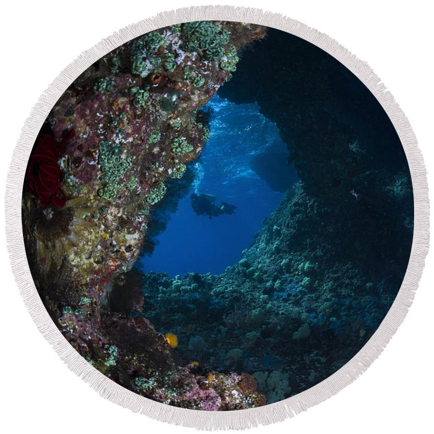 Diver Round Beach Towel featuring the photograph Diver At Boo Windows In Raja Ampat by Todd Winner