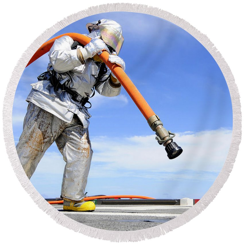 Us Navy Round Beach Towel featuring the photograph Firefighter Carries A Charged Hose by Stocktrek Images