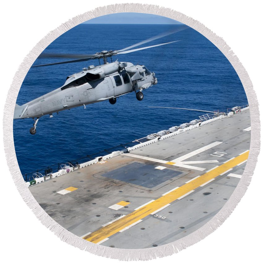 Us Navy Round Beach Towel featuring the photograph N Mh-60s Sea Hawk Helicopter Lifts by Stocktrek Images