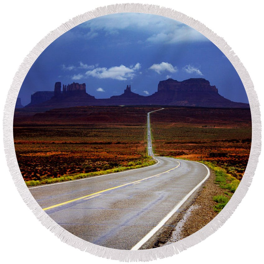 Monument Valley Round Beach Towel featuring the photograph Rainclouds Over Monument Valley by Ellen Heaverlo