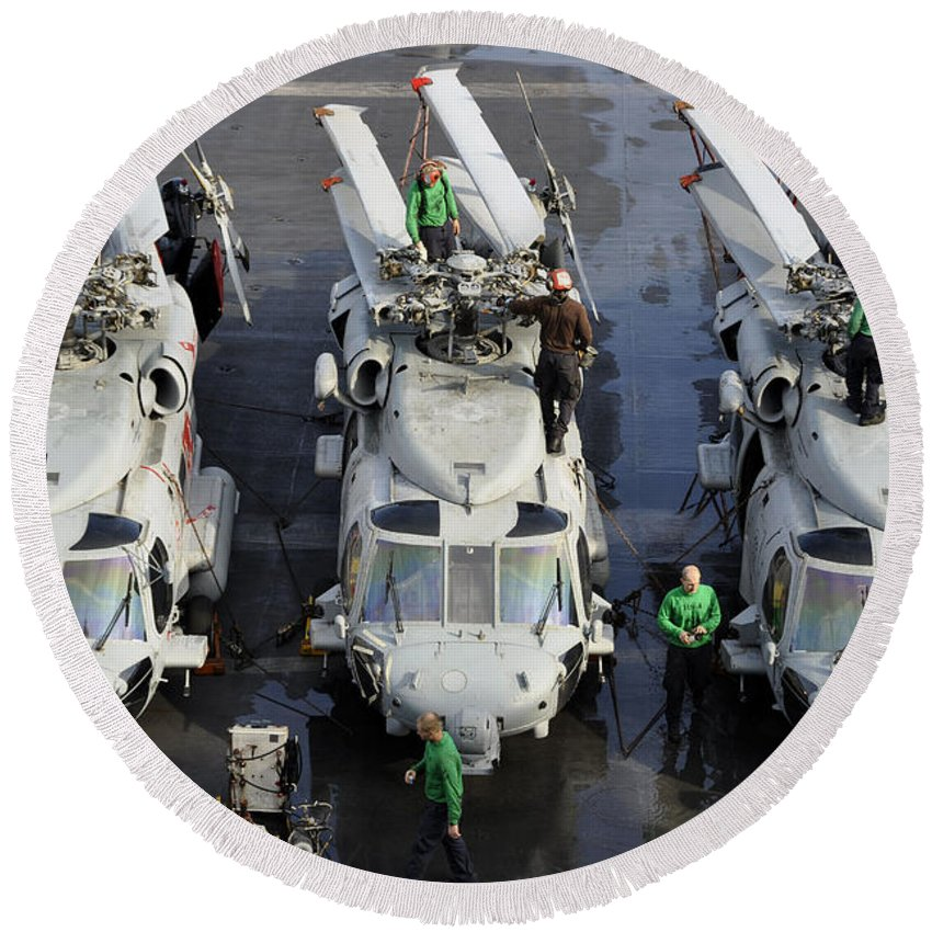 Aircraft Carrier Round Beach Towel featuring the photograph Sailors Perform Maintenance On Mh-60s by Stocktrek Images