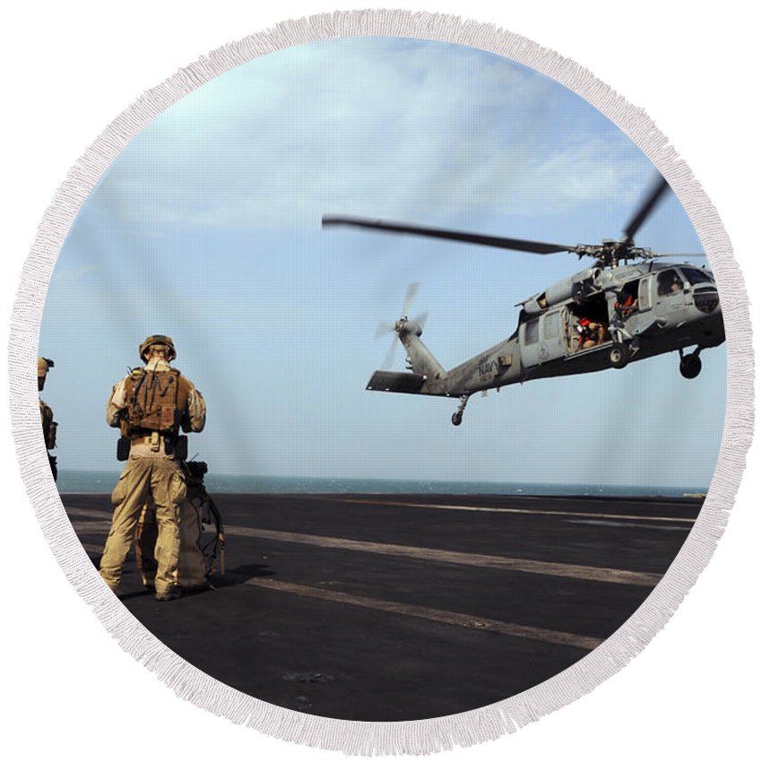 Aircraft Carrier Round Beach Towel featuring the photograph Sailors Prepare To Board An Mh-60s Sea by Stocktrek Images