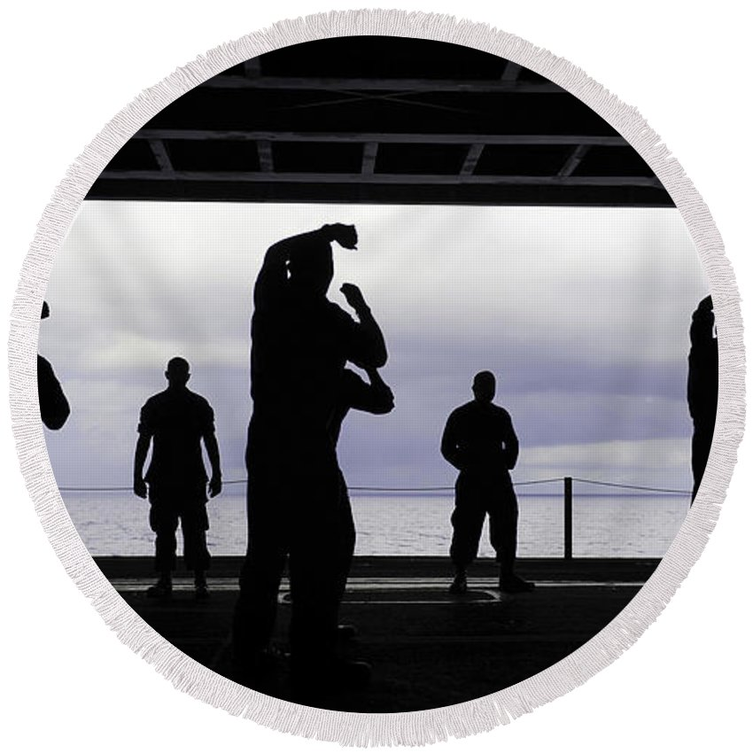 Military Round Beach Towel featuring the photograph Silhouette Of Sailors In The Hangar Bay by Stocktrek Images
