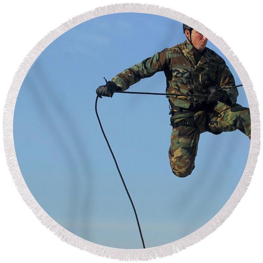Obstacle Course Round Beach Towel featuring the photograph Soldier Rappels Off A Tower While by Stocktrek Images
