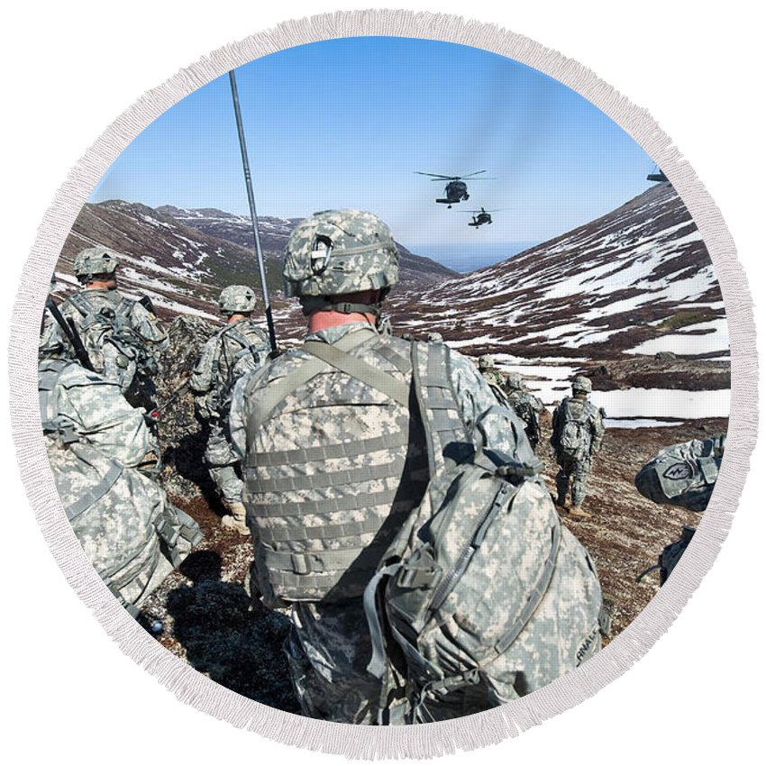 Army Round Beach Towel featuring the photograph Soldiers Wait For Uh-60 Black Hawk by Stocktrek Images