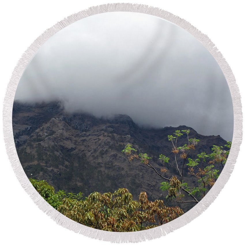 Tree Round Beach Towel featuring the photograph Trees And Leaves At The Base Of A Mountain With Clouds And Mist Covering The Top by Ashish Agarwal